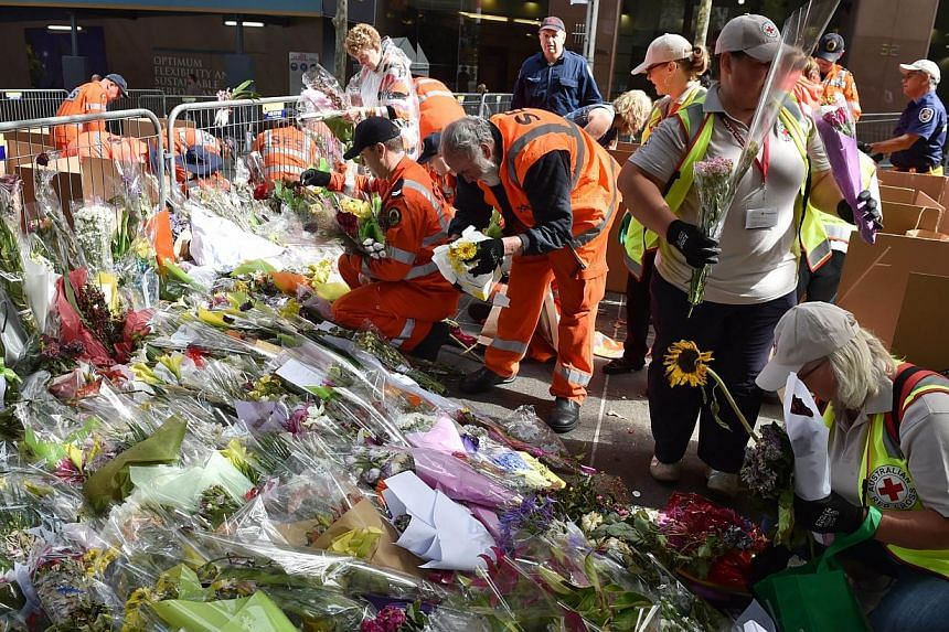 Flowers being removed at a memorial site outside the Lindt cafe in Sydney on Tuesday, one week after the siege which saw two hostages and the gunman killed. What is striking about such incidents is the everyday ordinariness of where the victims were