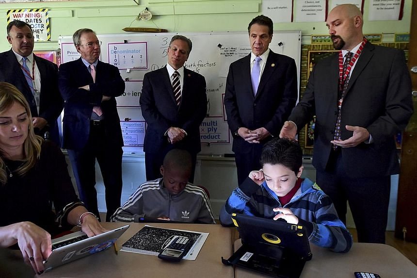 Google executive chairman Eric Schmidt (second from left) on a school visit to see how a New York class learns through technology. He says the upheavals from massive technological changes are rarely expected. -- PHOTO: REUTERS