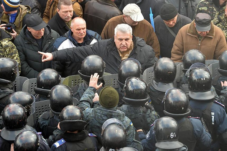 Protesters and police in Kiev, Ukraine. Russian President Vladimir Putin's revanchism in Ukraine's Donbas region has a disturbingly familiar ring to it – reminiscent of interwar Germany's own irredentist policies. -- PHOTO: AGENCE FRANCE-PRES