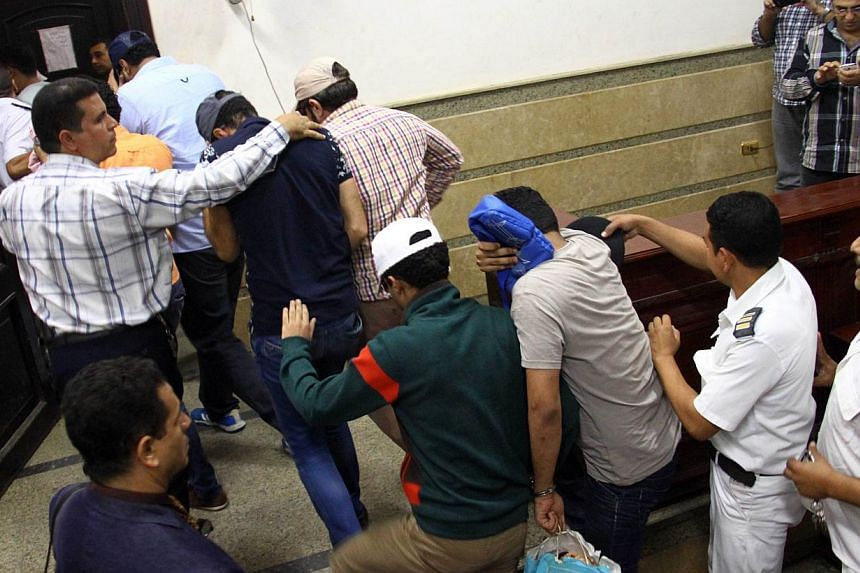 Egyptian men on trial for doing a video prosecutors claimed was of a gay wedding enter the courtroom in Cairo on Nov 1, 2014. -- PHOTO: AFP