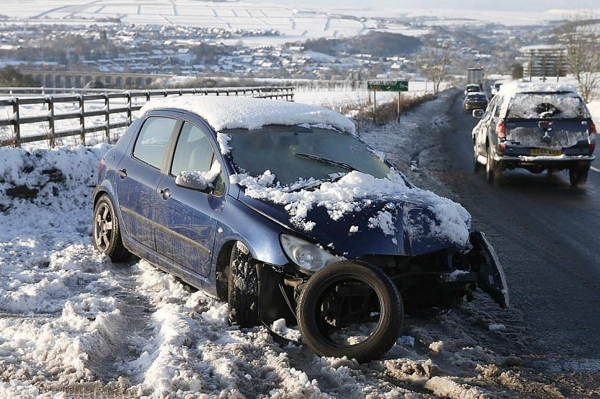 A crashed car stands abandoned on a snow covered verge near Sheffield, northern England on Dec 27, 2014. -- PHOTO: REUTERS