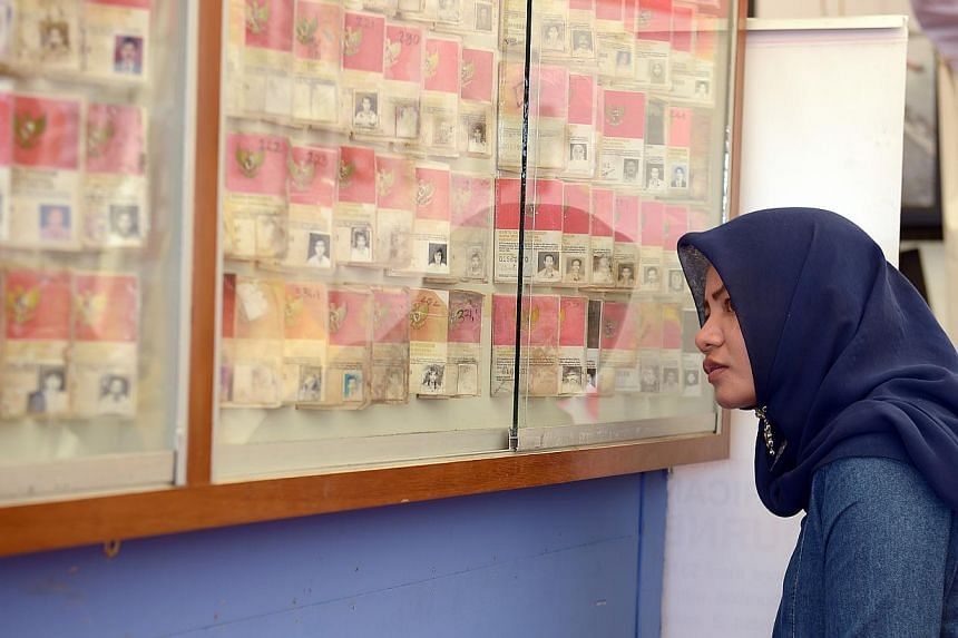 A lady looks at the identity cards of those who had perished during the 2004 tsunami, on Dec 26, 2014 at the Aceh Tsunami Commemoration Event in Banda Aceh.-- ST PHOTO: DESMOND WEE