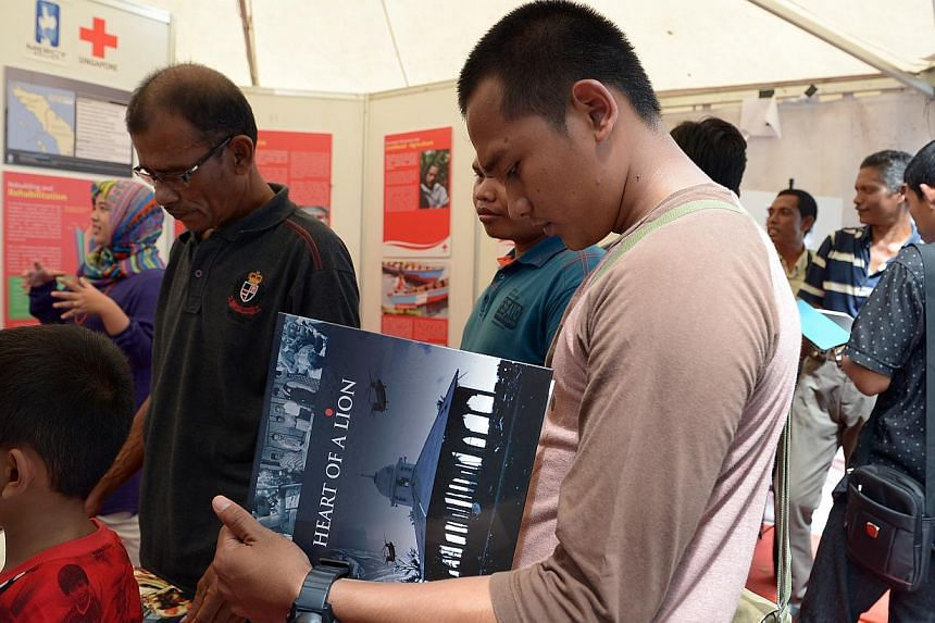Visitors at the Aceh Tsunami Commemoration Event browse through a photobook at the Mercy Relief booth on Dec 26 2014.-- ST PHOTO: DESMOND WEE