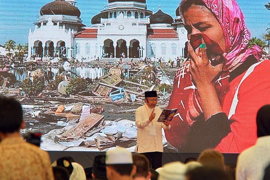 An Acehnese resident recalling what happened during the 2004 catastrophe, at the Aceh tsunami commemoration event in Banda Aceh on Dec 26, 2014 .-- ST PHOTO: DESMOND WEE