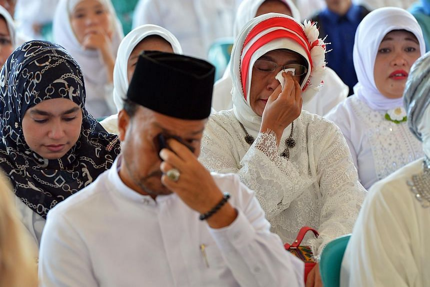 Acehnese wept during the Aceh Tsunami Commemoration held at Blang Padang in Banda Aceh on Dec 26, 2014.-- ST PHOTO: DESMOND WEE