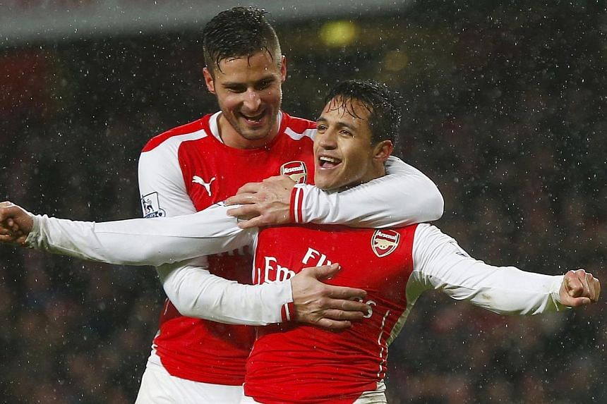 Arsenal's Alexis Sanchez (front) celebrates with team-mate Olivier Giroud after scoring a goal against Queens Park Rangers during their English Premier League soccer match at the Emirates Stadium in London Dec 26, 2014. -- PHOTO: REUTERS
