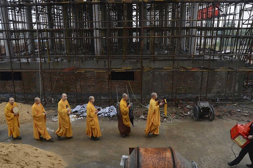 Monks chant sutras for a half-way built Buddhist temple donated by a property developer in Jiaxing, Zhejiang province on Oct 31, 2014. -- PHOTO: REUTERS