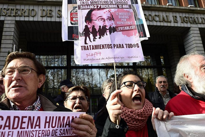 Hepatitis C sufferers and supporters hold placards during a demonstration outside Spain's health ministry on Dec 27, 2014, complaining that they are being denied access to a new drug that could cure them of the deadly liver disease. -- PHOTO: AFP