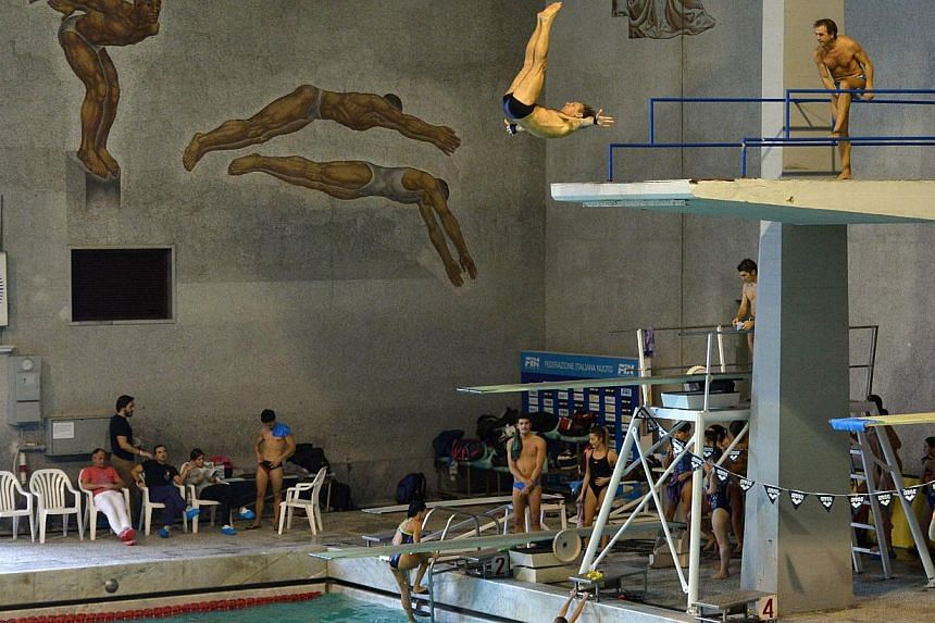 Marco Fois (middle, top) trains at a swimming pool at Foro Italico in Rome on Dec 20, 2014. -- PHOTO: AFP