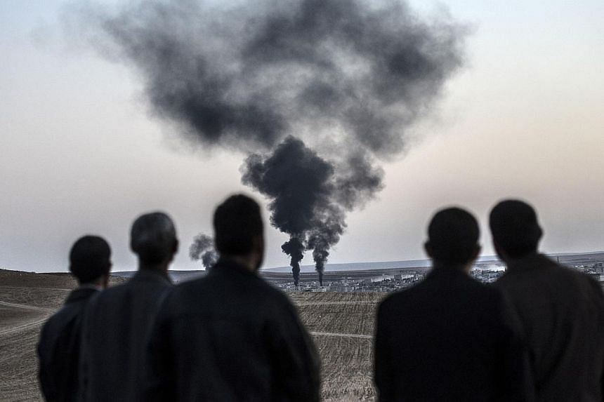 People watch as smokes rises from the town of Kobane, also known as Ain al-Arab, on Oct 26, 2014, at the Turkish border near the southeastern village of Mursitpinar, Sanliurfa province. -- PHOTO: AFP