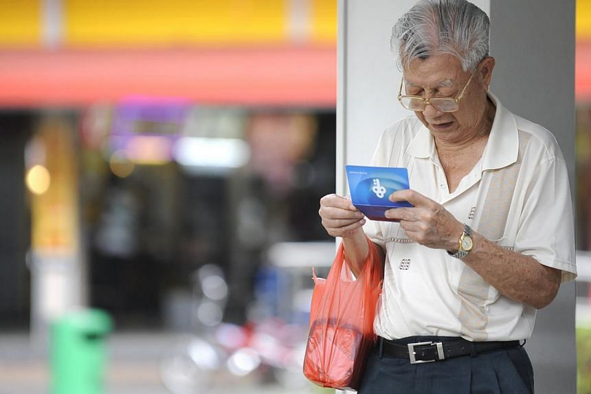 An elderly man concentrates on the figures in his bank account book. Workers can expect a small boost to their Central Provident Fund savings from Jan 1. --STPHOTO: ASHLEIGH SIM
