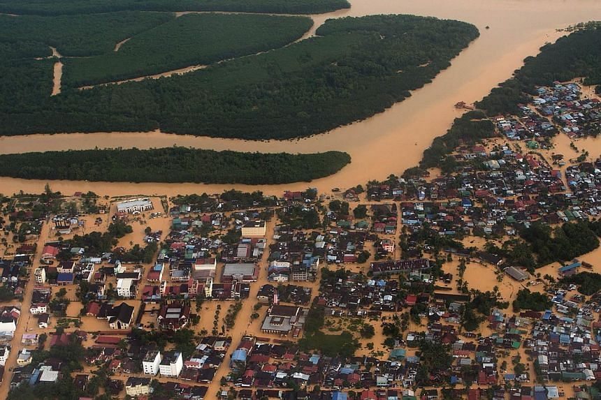 This aerial view shows houses and plantations submerged in floodwaters in Pengkalan Chepa, near Kota Bharu on Dec 27, 2014. -- PHOTO:AFP