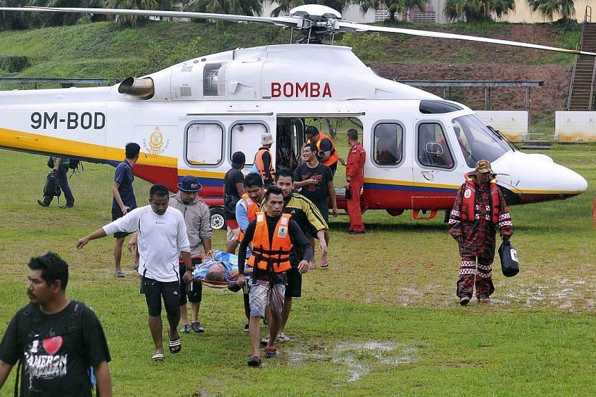 Volunteers carry a man on a stretcher out of a helicopter during a mission to evacuate elderly people from the National Park in Kuala Tahan, to Jerantut, Pahang on Dec 24, 2014. -- PHOTO: REUTERS