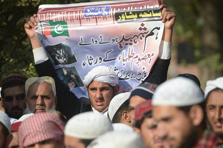 Pakistani Islamists gather for the victims of the Peshawar school massacre in front of the radical Red mosque after congregational Friday prayers in Islamabad on Dec 19, 2014. -- PHOTO: AFP