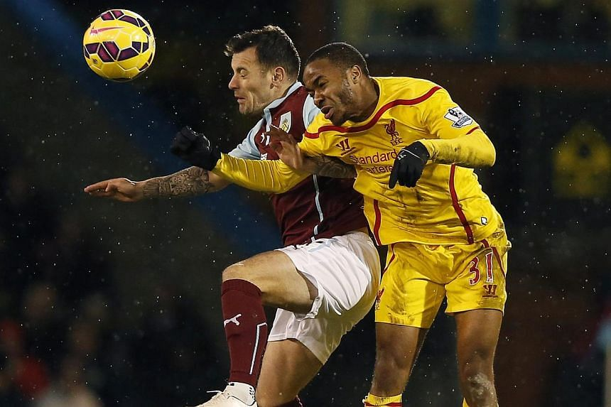 Burnley's Ross Wallace (left) is challenged by Liverpool's Raheem Sterling during their English Premier League soccer match at Turf Moor in Burnley, northern England Dec 26, 2014. -- PHOTO: REUTERS