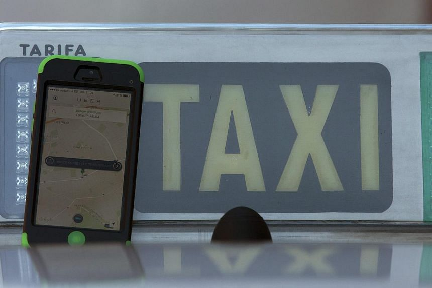 The car-sharing service app Uber on a smartphone next to a taxi sign is seen in this photo illustration taken in Madrid on Dec 10, 2014.Uber vowed Friday to keep operating in Spain despite a ban following a lawsuit by taxi drivers and said it w