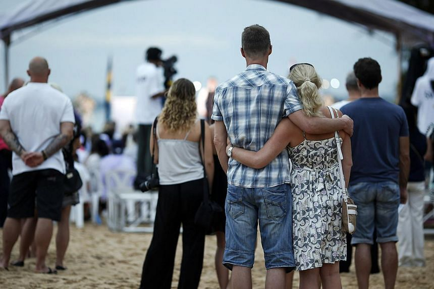 People attend a Swedish memorial service for victims of the 2004 tsunami at a beach in Khao Lak, Thailand on Dec 26, 2014. -- PHOTO: REUTERS