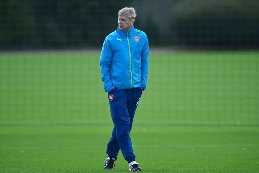 Arsenal's French manager Arsene Wenger attends training at their London Colney facility in Hertfordshire, north of London on Oct 21, 2014. He admits losing Oliver Giroud once again is a body blow to Arsenal's Champions League push. -- PHOTO: AFP