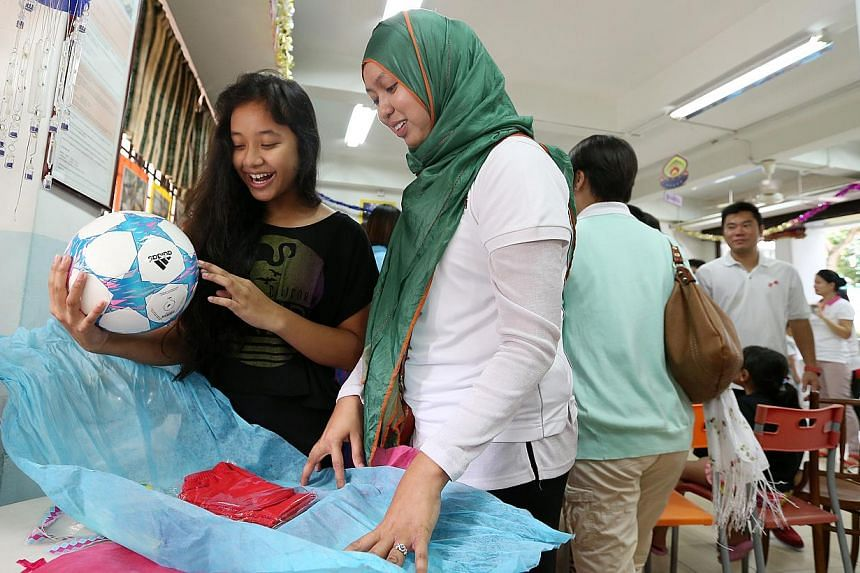 Nadia Adriana (left) with her new football as her New Year wish. Nanyang Girls' High School's teacher Ms Nur Hanim Mohamed (in white) watches by the side. -- ST PHOTO:NEO XIAOBIN