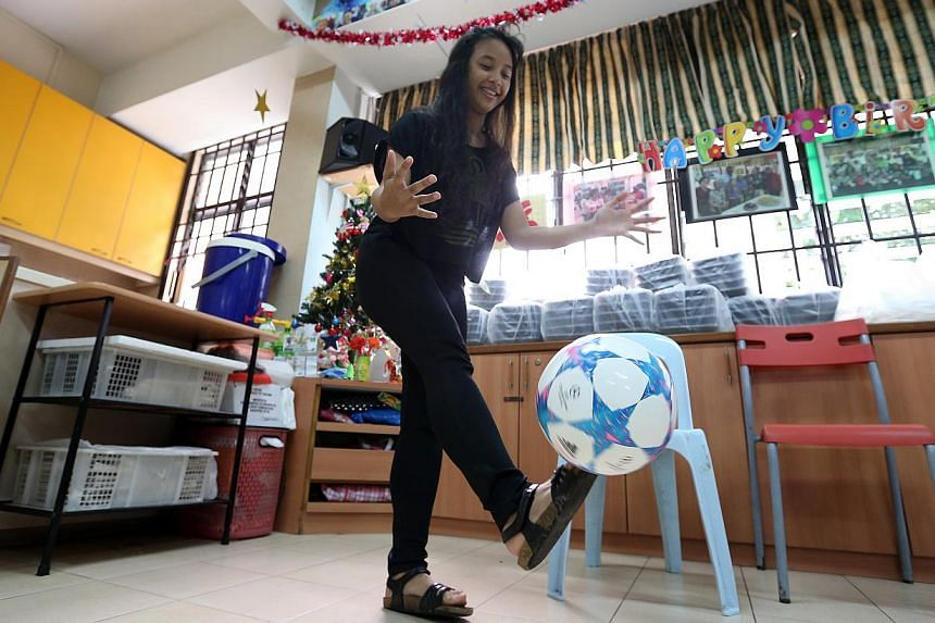 Nadia Adriana playing with her new football at Sunlove Senior Activity Center (Marsiling) on Dec 27, 2014.-- ST PHOTO:NEO XIAOBIN