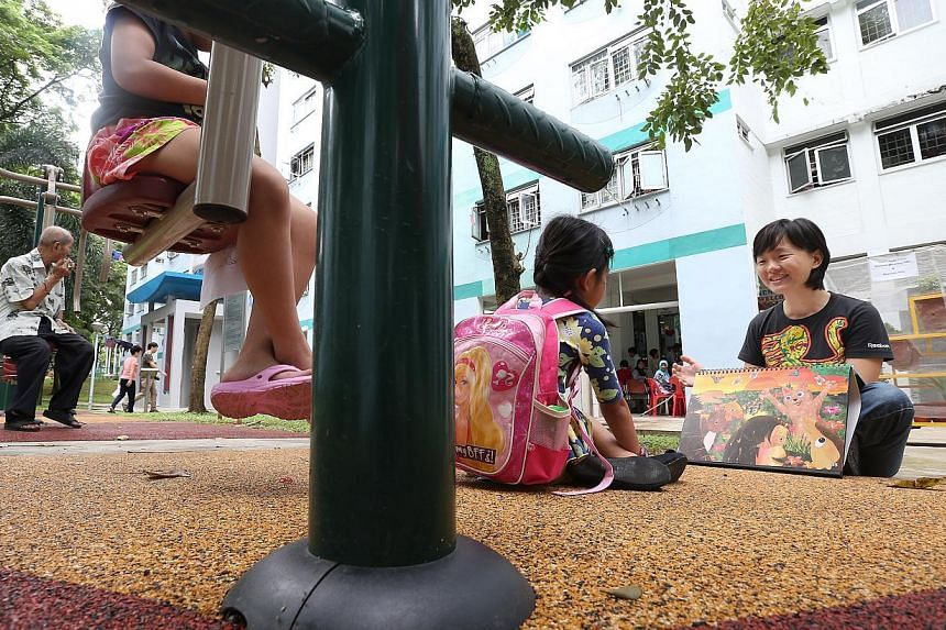 Nanyang Girls' High School teacher Ms Gloria Teng (extreme right) reads to one of the low-income children near the Sunlove Senior Activity Center (Marsiling).-- ST PHOTO:NEO XIAOBIN
