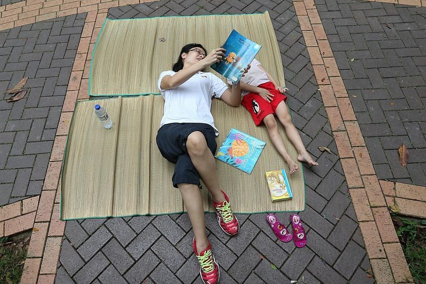 Nanyang Girls' High School teacher Ms Serene Sng (left) reads to one of the low-income children as they lie on picnic mattresses near the Sunlove Senior Activity Center (Marsiling).-- ST PHOTO:NEO XIAOBIN