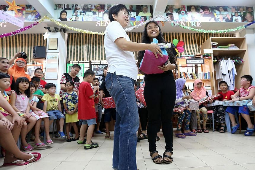 Nadia Adriana (in black) receives her gift of a brand new football as her New Year wish, from Nanyang Girls' High School's senior head for student development Mrs Chua Mei Hong (in white). -- ST PHOTO:NEO XIAOBIN