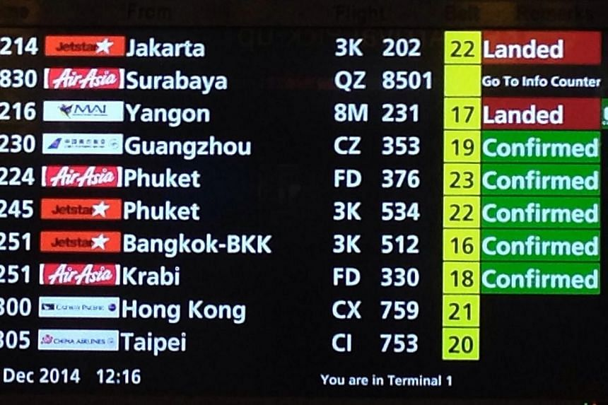 The electronic screen at Terminal 1 arrival hall showing the details of the AirAsia flight QZ8501 bound for Singapore from Surabaya that lost contact. -- ST PHOTO: NEO XIAOBIN