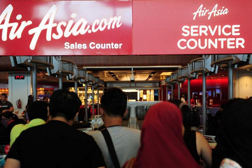 People queue at an AirAsia sales counter in terminal 1 at Changi international airport in Singapore on Dec 28, 2014. An illness of the family patriarch led to the Singapore trip of one Indonesian family being cancelled - and in turn saved their