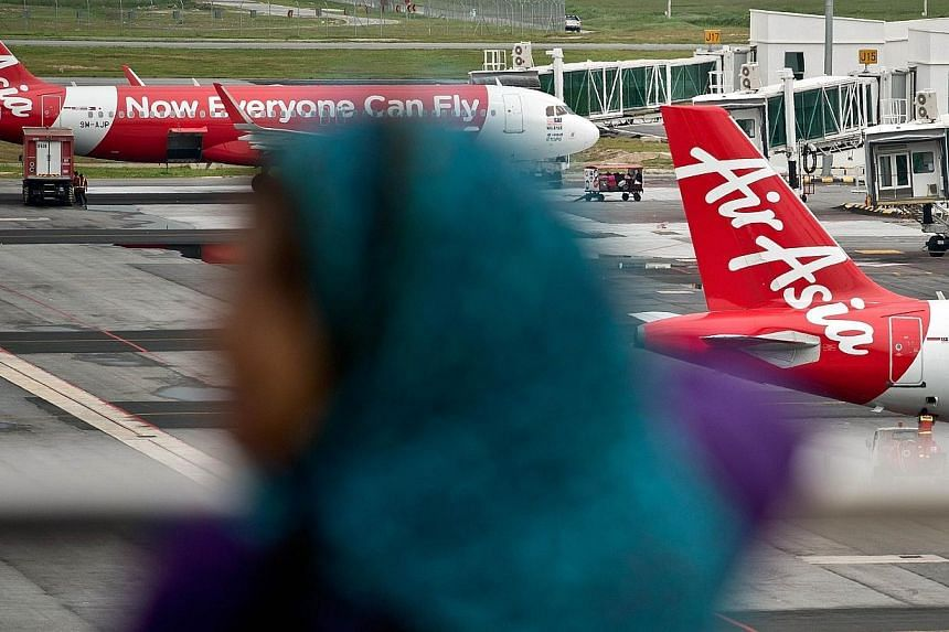 A Malaysian woman watches AirAsia Airbus A320 airplanes parked on the tarmac at the low-cost carrier Kuala Lumpur International Airport 2 (KLIA2) in Sepang on Dec 28, 2014. -- PHOTO: AFP