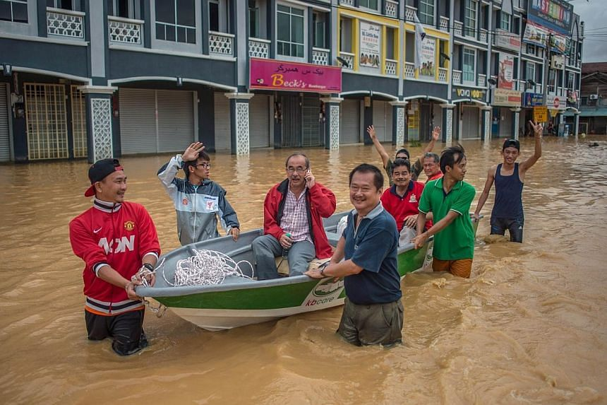 Local residents use a boat to cross floodwaters in Kota Bahru on Dec 28, 2014. -- PHOTO: REUTERS
