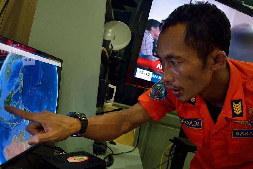 """An official from Indonesia's national search and rescue agency in Medan, North Sumatra points at his computer screen to the position where AirAsia flight QZ8501 went missing on Dec 28, 2014. An American aviation expert has said that it is """"standard p"""