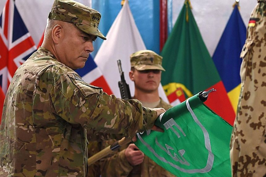 US General John Campbell (left) rolls the flag of the NATO-led International Security Assistance Force (ISAF) during a ceremony marking the end of ISAF's combat mission in Afghanistan at ISAF headquarters in Kabul on Dec 28, 2014.The US command