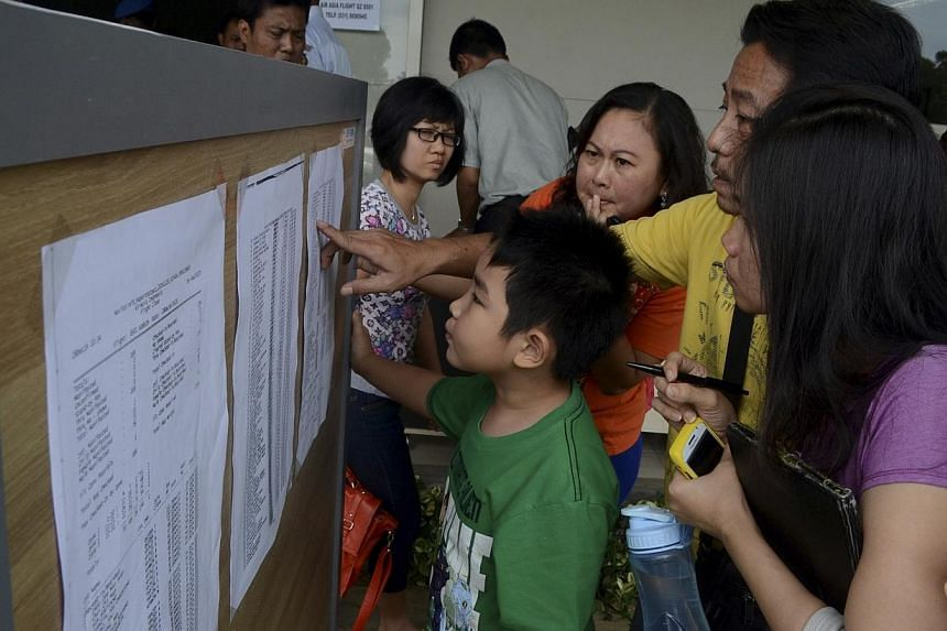 Family members of passengers on board AirAsia flight QZ 8501 look at a passenger list inside a crisis centre at Juanda Airport in Surabaya, East Java on Dec 28, 2014 in this photo taken by Antara Foto. -- PHOTO: REUTERS