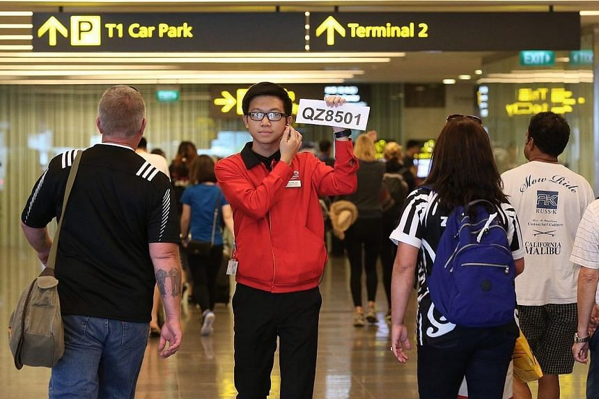 A Changi Airport staff holds up a sign to direct relatives of passengers of AirAsia flight QZ8501 to the holding area. -- ST PHOTO: NEO XIAOBIN