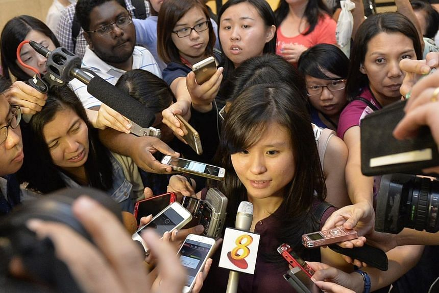 Louise Sidharta, 25, whose fiance was on the missing AirAsia flight QZ8501 speaking to the media outside the holding room for relatives and next-of-kin at Changi Airport Terminal 2, on Dec 28, 2014. -- ST PHOTO: DESMOND FOO