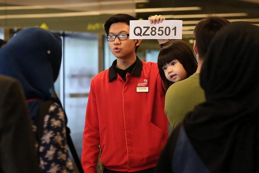 "An airport staff holding up a ""QZ8501"" sign at the Skytrain lobby in Terminal 2 to direct potential family members and friends seeking information on the AirAsia flight QZ8501 bound for Singapore from Surabaya that lost contact. -- ST PHOTO: NEO XIAO"