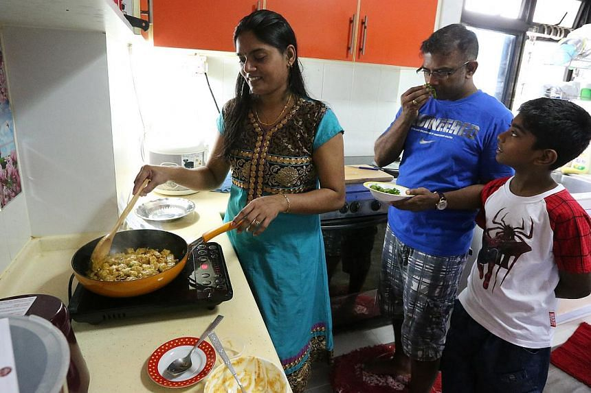 (From far left) Mrs Shantha Prabahar cooks with her husband, Mr Prabahar Annalingam, and son Shanthosh using a meal kit from The Hungry Chef. -- PHOTO: NEO XIAO BIN
