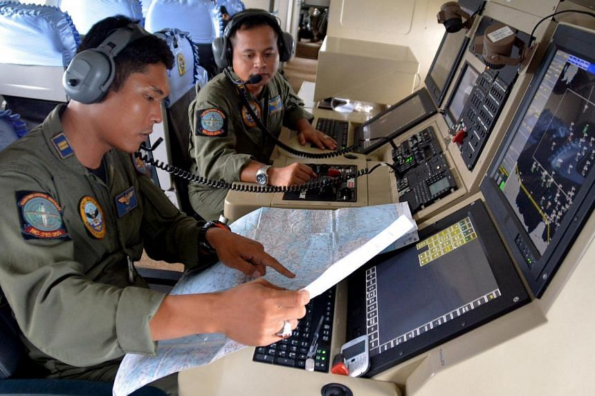 Two members of the Indonesian Navy's Tactical Commanding Operator (TACCO) help with the search for AirAsia flight QZ 8501 on board a CN235 aircraft over Karimun Java, in the Java Sea on Dec 28, 2014 in this photo taken by Antara Foto. -- PHOTO: REUTE