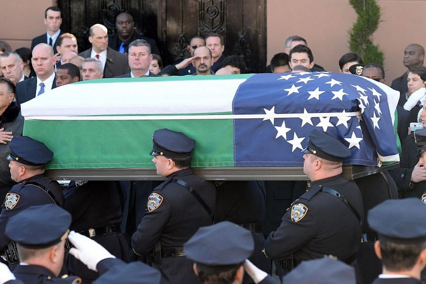 The casket of New York Police officer Rafael Ramos is carried out of Christ Tabernacle church on Dec 27, 2014 in New York. Thousands of people, including US Vice-President Joe Biden, attended the funeral on Saturday for Ramos, one of two New York off