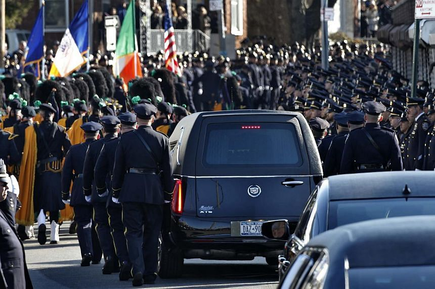 A hearse carrying the casket containing the body of slain New York Police Department officer Rafael Ramos departs the Christ Tabernacle Church to it's final resting place in the Queens borough of New York Dec 27, 2014. -- PHOTO: REUTERS