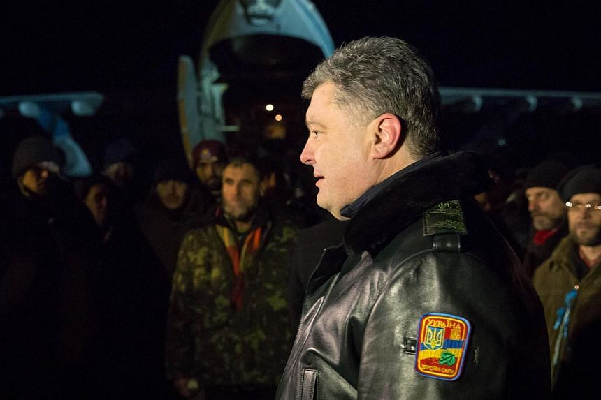 Ukrainian President Petro Poroshenko (right) welcomes Ukrainian troops freed from captivity after they arrive at an airport near Kiev early on Dec 27, 2014. -- PHOTO: AFP