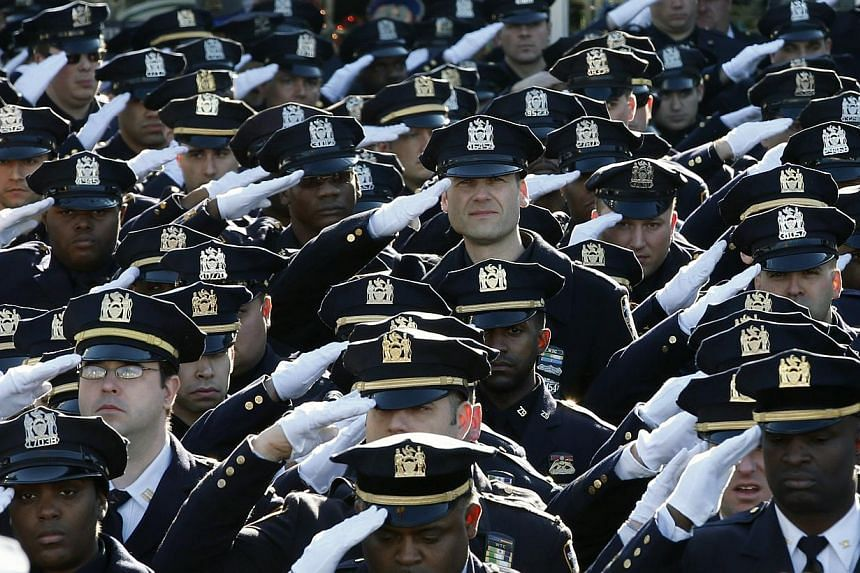 Police salute outside the Christ Tabernacle Church as the casket of slain New York Police Department officer Rafael Ramos is carried from the church following his funeral service in the Queens borough of New York on Dec 27, 2014. -- PHOTO: REUTERS