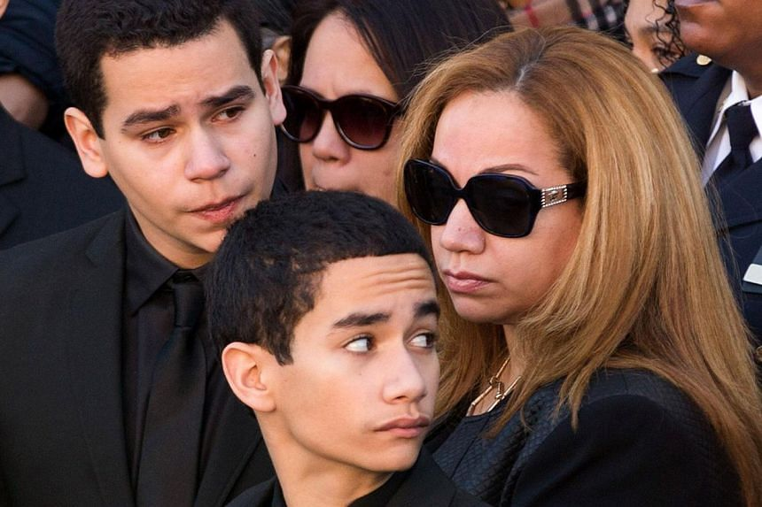 Maritza Ramos, wife of the victim, is joined by her sons Justin (left) and Jaden (centre) during the funeral of slain New York Police Department officer Rafael Ramos at the Christ Tabernacle Church on Dec 27, 2014 in the Glenwood section of the Queen