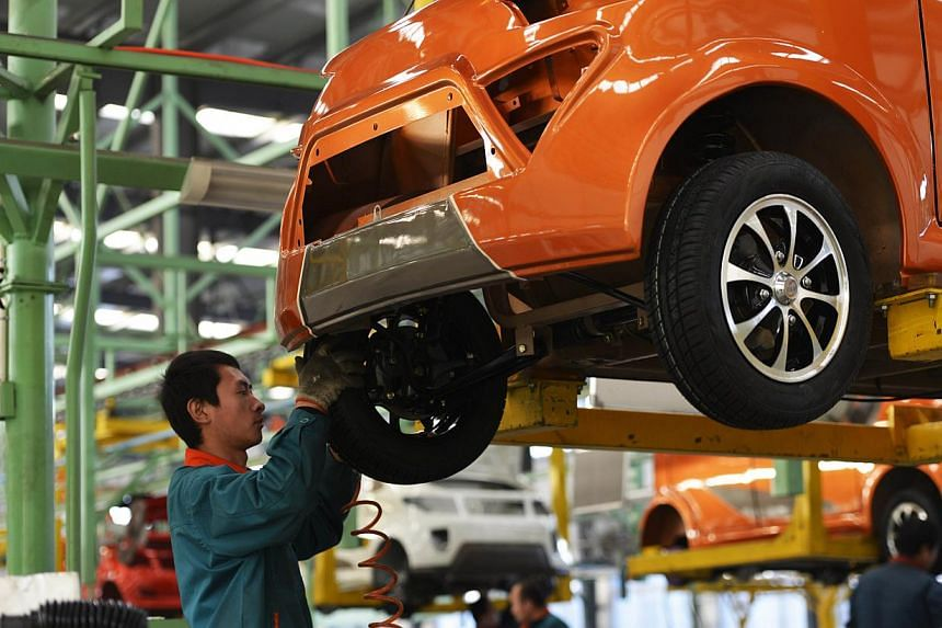 Workers assemble automobiles in a factory in Zouping, east China's Shandong province on Dec 16, 2014. The China National Bureau of Statistics will release the manufacturing PMI for December on New Year's Day. -- PHOTO: AFP