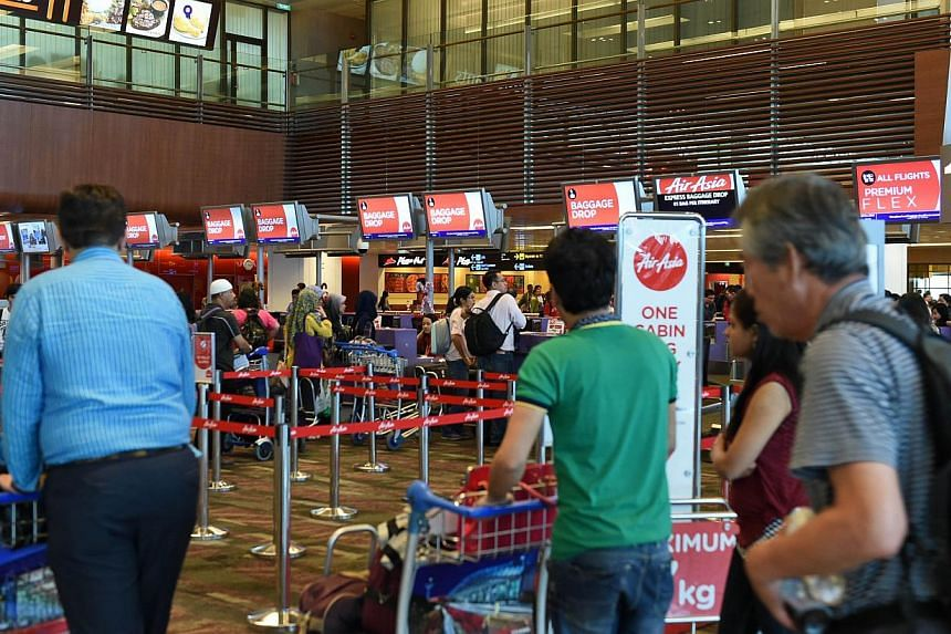 Passengers queue at the AirAsia check-in counter before their departure at Singapore Changi airport terminal on Dec 28, 2014. -- PHOTO: AFP