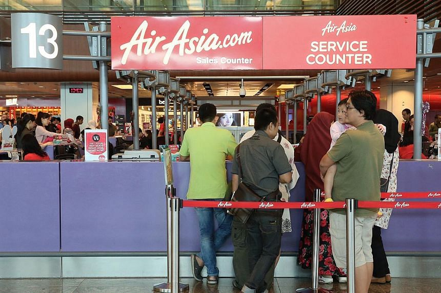 Passengers at the AirAsia counters at Terminal 1 arrival hall. -- ST PHOTO: NEO XIAOBIN