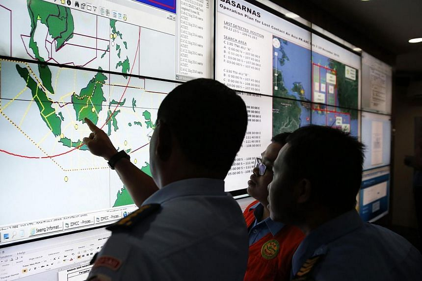 Military and rescue authorities monitor progress in the search for AirAsia Flight QZ8501 in the Mission Control Center inside the National Search and Rescue Agency in Jakarta on Dec 29, 2014. -- PHOTO: REUTERS