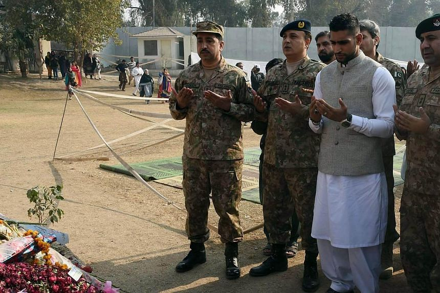 British boxer Amir Khan (second from right) prays along with Pakistani militarty officials at the memorial of the army-run school where 150 people were massacred by the Taliban, in Peshawar on Dec 29, 2014. -- PHOTO: AFP