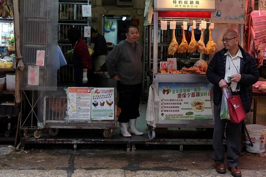 A worker (centre) sells live chickens at a shop in the Wan Chai district of Hong Kong on Dec 28, 2014.A man has died from the H7N9 bird flu strain in Zhejiang province, in eastern China, state media reported on Monday, Dec 29, 2014, at the end